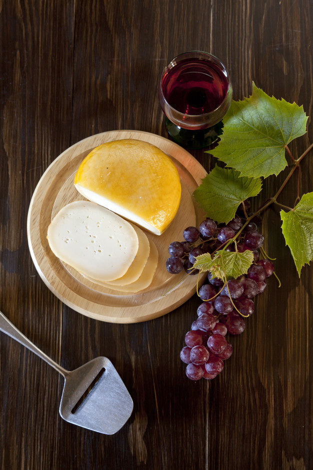Red Grapes with leaves, glass of wine and fresh cheese on rustic